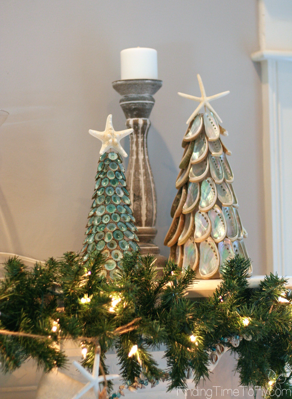 Coastal Christmas Keeping Room with elegant fireplace mantle, seashell Christmas trees, starfish garland and seashell ornaments